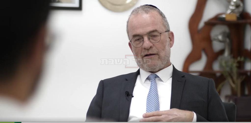 הרב אקשטיין בשיחה עם בעז, כשברקע ''התפילה''