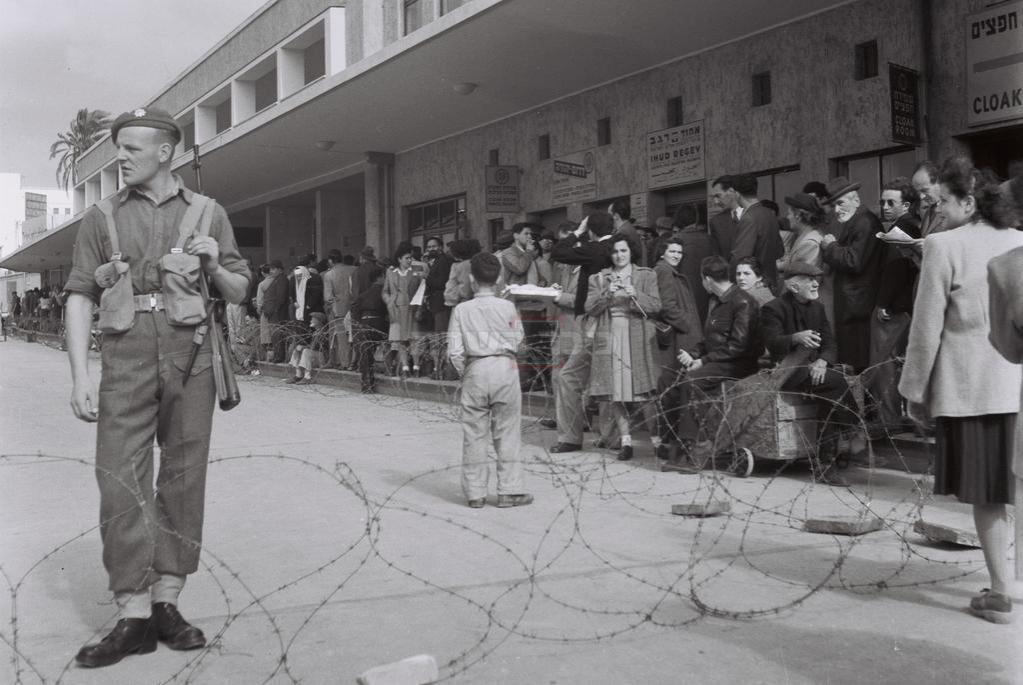 חייל בריטי שומר ליד גדר התייל בתחנת האוטובוסים המרכזית של תל אביב, בזמן העוצר שהטילו הבריטים על העיר (צילום: KLUGER ZOLTAN, לע''מ)
