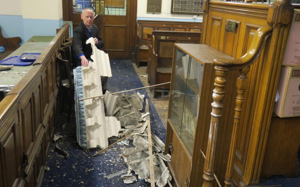נשיא בית הכנסת ליאון סילבר מחזיק בידו שברי תקרה