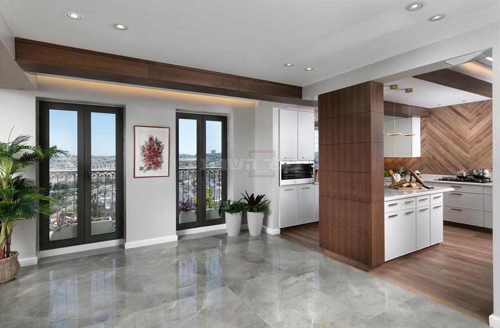מראה העץ החמים גולש מתוך המטבח אל פני הסלון לשמירת הרצף העיצובי (צילום: אלעד גונן)