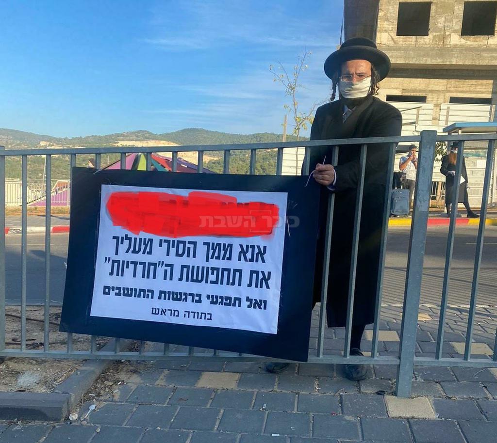 החשוד, עם שלט מחאה נגד השוטרת החרדית (באדיבות המצלם)