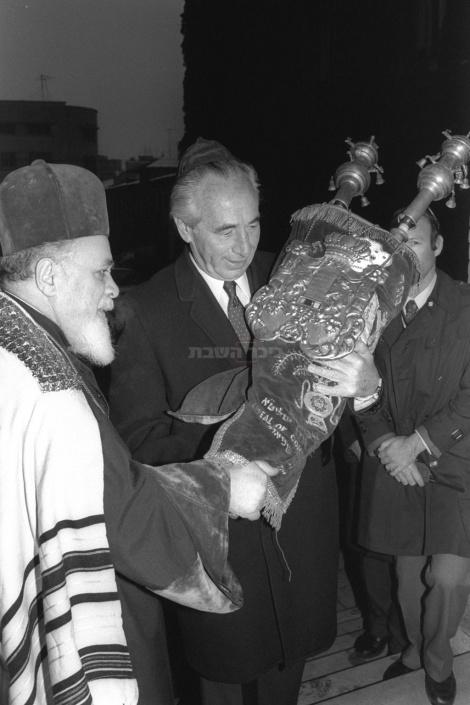 """רה""""מ פרס מחזיק בספר תורה שקיבל מהרב הראשי הרומני בבית הכנסת הגדול בבוקרשט ב-1985"""