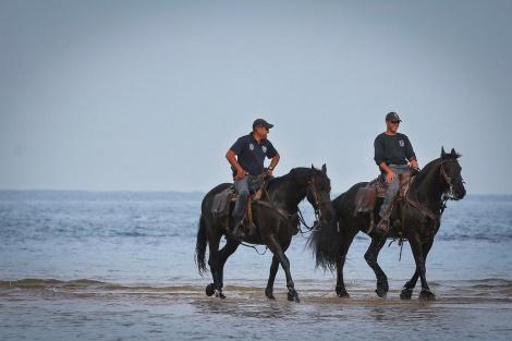 שוטרים ישראלים רוכבים על סוסים בחוף הים באשקלון (צילום: יעקב לדרמן / פלאש 90)