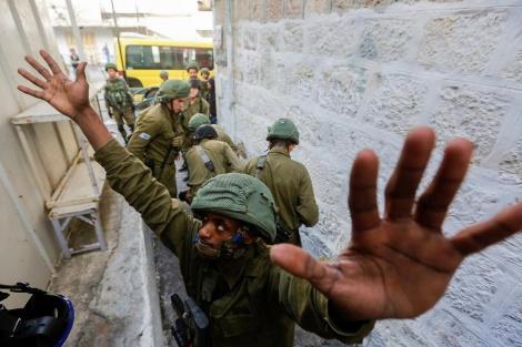 """חיילי צה""""ל מעכבים צעיר פלסטיני במהלך עימותים בחברון בעקבות מחאה פלסטינית על החלטת הנשיא האמריקאי דונלד טראמפ להכיר בירושלים כבירת ישראל (צילום: ויסאם השלמון / פלאש 90)"""