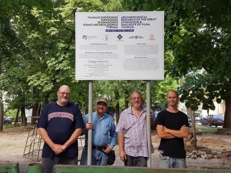 מנהלי החפירה ליד השלט שהציבה עיריית וילנה באתר החפירה.