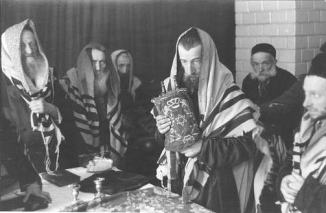 תפילה בגטו, יהודים עטורי טלית סביב שולחן עם ספר תורה