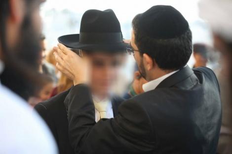 הרב משה כהן מיד לאחים חובש את המגבעת לראשו של חתן הבר מצווה. צילום: יד לאחים