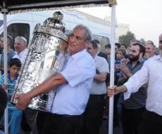 הזוכה עם ספר התורה בתהלוכה ברחובה של עיר - הכנסת ספר תורה לזוכים בהגרלת יד לאחים