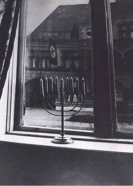 החנוכייה אל מול דגלי הנאצים (מתוך אתר יד ושם)