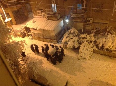 הרב מורגנשטרן צועד עם חסידיו, בשלג (צילום: יחיאל)