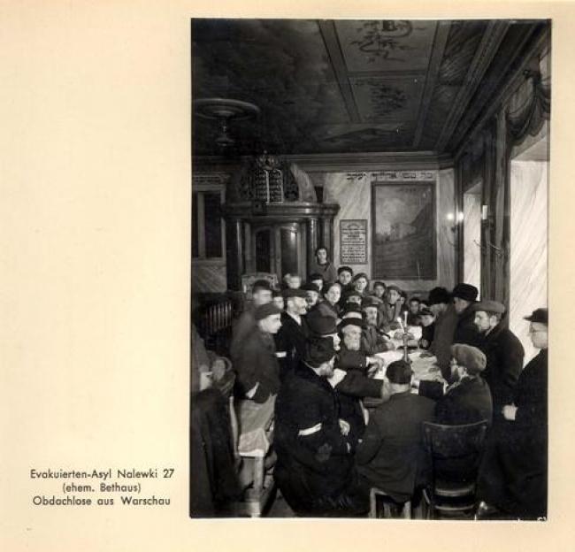 יהודים לומדים תורה סביב שולחן שעליו מונחים פמוטים...