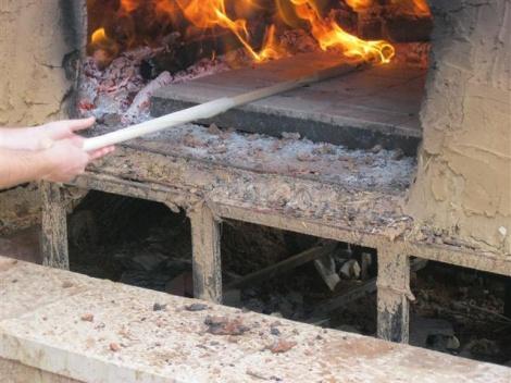 את המצה משטחים בתוך התנור. החום האדיר בתנור, מבעיר את הנייר שעל המקל.