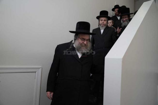 הרבי מסקולען מלווה במדרגות