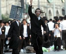 צעיר חרדי זורק חפצים בהפגנה. צילום: פלאש 90