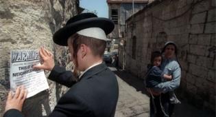 נער מדביק מודעה על קיר ירושלמי. צילום: פלאש 90