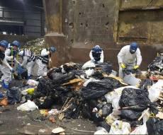 המתנדבים החרדים מחטטים בתכולת משאית האשפה