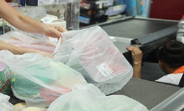 לקוחות אורזים מצרכים בשקיות ניילון בקופה