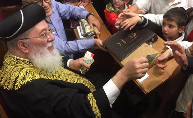 צפו: רבה של ירושלים קרא מגילה וחילק שטרות כסף