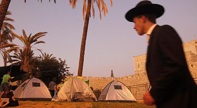 חרדי חולף על פני המאהלים בירושלים, היום