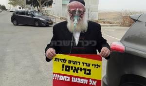 מסכת חמצן ושלט מחאה - מסכות חמצן ומחאה: בערד נערכים להפגנה