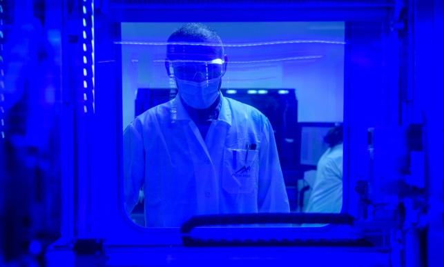 טכנאים מבצעים בדיקת קורונה במעבדה