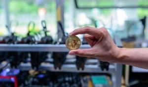 מטבע ביטקוין על רקע חוות כרייה