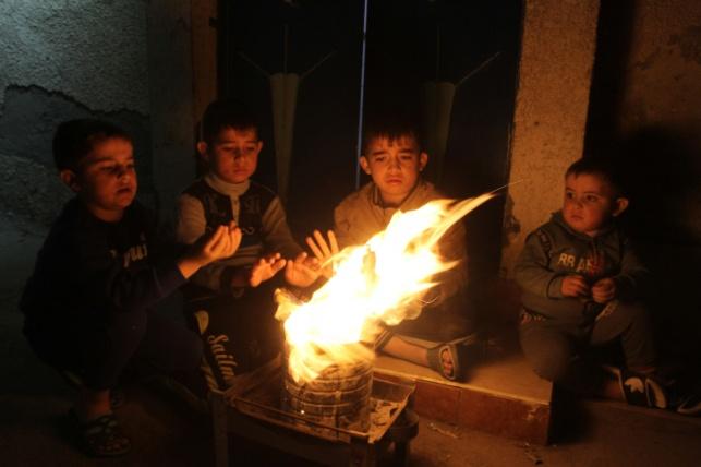 ילדים עזתיים מתחממים ליד מדורה ממחסור בחשמל
