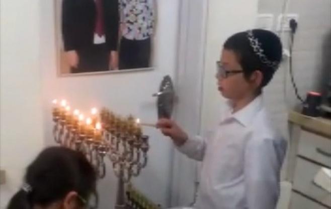 הילד מוישי הולצברג מדליק נרות חנוכה. צפו