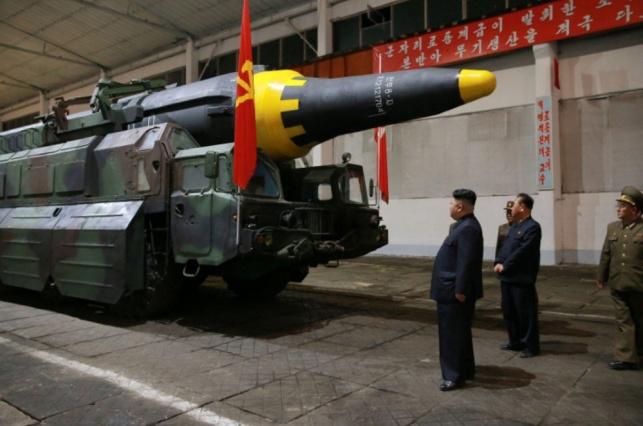 קים ג'ונג און בוחן את אחד הטילים