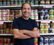 רמי לוי, על רקע מדף מוצרים באחת מחנויותיו