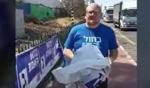 צפו: פעיל 'כחול לבן' תולש מודעות  של ג'