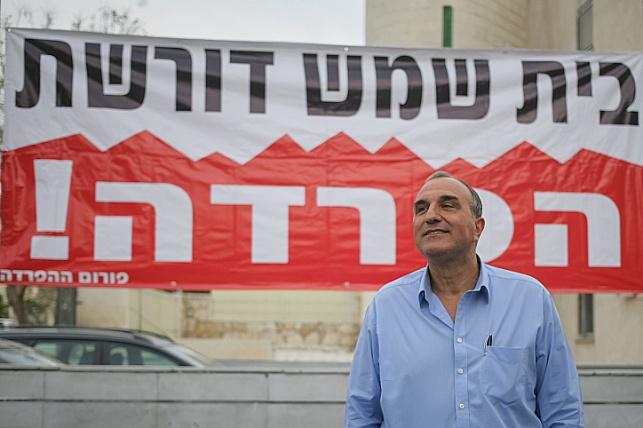 אלי כהן על רקע שלט הדורש הפרדה בבית-שמש