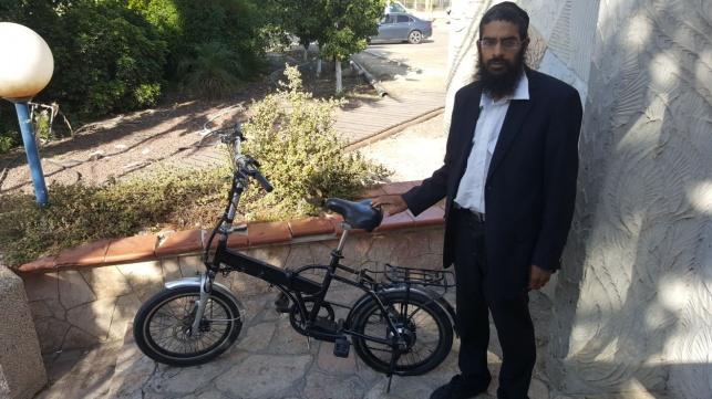 הבעלים לצד האופניים שהושבו לו