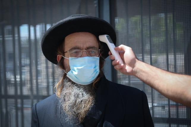 בדיקת חום לחרדי עם מסכה. תמונת אילוסטרציה