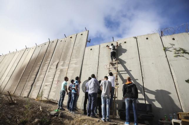 פלסטינים מטפסים על חומת ההפרדה במחסום קלנדיה
