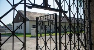 שער הכניסה למחנה דכאו. על הדלת רשומות המילים 'העבודה משחררת'