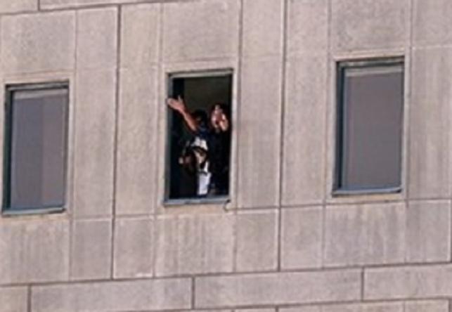 אחד המחבלים נראה מחלון הפרלמנט, מנופף כנראה בבן ערובה