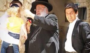 """הגר""""ב שמואלי גוזר משערותיו של בלום. מימין: עוזרו ר' מרדכי חסידים"""