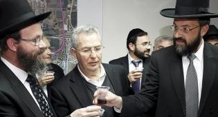 מימין: הרב אטיאס והרב הלוי מרימים כוסית. בתווך: ראש-העיר