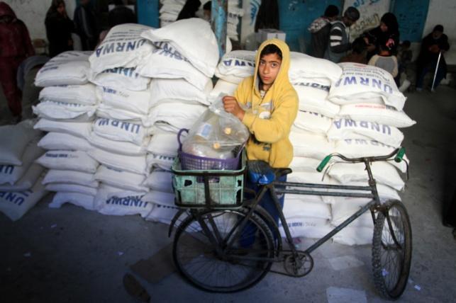 ילד עזתי ליד חבילות מזון מסוכנויות הסיוע