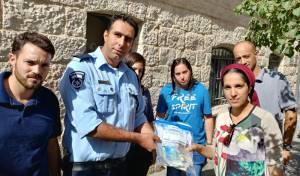 האישה מקבלת את כספה בחזרה, מידי השוטרים