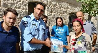 האישה מקבלת את כספה בחזרה, מידי השוטרים - עובד גנב כסף מהמעסיקה והחביא בחניון