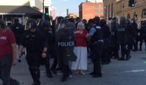 שוטרים עוצרים את אחת המפגינות