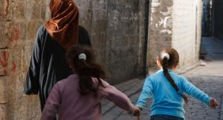 אישה וילדים בסמטאות חאלב. ארכיון - דיווחים: צבא סוריה ביצע הוצאות להורג אכזריות