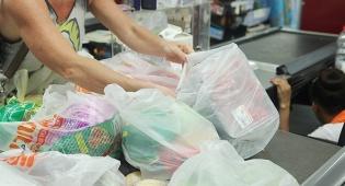 לקוחות אורזים מצרכים ב שקיות ניילון ב קופה ב סניף ויקטורי ב תל אביב - רשת הסופרמרקטים טסקו תפסיק לחלוטין את אספקת שקיות הניילון לקונים